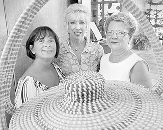 """The Vindicator/William D. Lewis HAVING A PARTY: Framed in one the baskets that is on display as part of the """"A Southern Bash"""" summer garden party planned by Friends of Fellows Riverside Garden are committee members, from left, Sharon Letson and Becky Tennant and event chair Catherine Powers."""