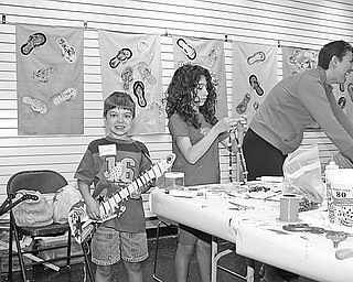 Special to The Vindicator CRAFTY KIDS: Trumbull Art Gallery in Warren was the setting for Summerfest 2009, which concluded July 1 with a parade and display of crafts at Courthouse Square. During the two-week program, children had the opportunity to create unique arts and crafts. In the top photo, Dante Byrne of Girard displays the guitar he made, while his sister, Francesca Byrne, concentrates on her bead-stringing project. In the bottom photo, Lauren Ulrich of Toledo, at left, and Lauren Kromer of Howland show off the guitars and one-of-a-kind hats they made during the Summerfest. At right in both pictures is Lauren's mother, Stephanie Kromer, who assisted the young crafters.