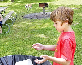 """Coulton Lockner, 12, of Lake Milton, tosses trash into a barrel at Lake Milton State Park. Lake Milton is one of the area parks not participating in the """"Carry In Carry Out"""" program."""