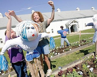 "Erica Shirilla, age 10, and her mother, Andrea Shirilla, both of Boardman, put the final pieces of tape on Dolly, a scarecrow named for her resemblence to the country singer Dolly Parton, that overlooks their garden plot at the Mill Creek MetroPark Farm in Canfield on Wednesday morning. Erica, who attends the children's gardening program every Wednesday has also talked her parents into allowing her to have a garden at home. ""I'm independent,"" says Erica whose favorite vegetable to grow is onions because she likes them in salsa, ""I've never been to a place where you can have your own garden and you can do it all yourself."" ""Every Wednesday, I get to harvest and get food,"" says Erica, ""Its fun."""