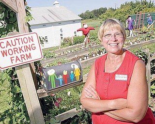 "Lynn Zocolo, Asst. Horticulture Educator, stands for a portrait outside the gardens at the Mill Creek MetroParks Farm in Canfield on Wednesday afternoon. ""These kids are learning when theyre having fun, entertainment is part of it,"" says Zocolo who also encourages education by having children grow new and different kinds of plants including bok choy, dinosaur kale, and red noodle beans, ""but I just love to see them smile,"" she adds."