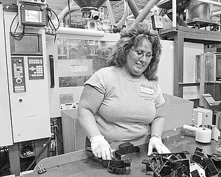 Venture Plastics employee Joanne Streets examines automotive brackets produced at the Newton Falls plant. The company is celebrating 40 years in business.