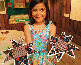 """Ridley Clark, 6, of Youngstown displays her finished quilts pieces that will be put together for a quilt at  the Mahoning Valley Historical Society's """"Pioneer Days"""" Summer Camp."""