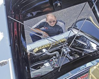 Jake Rodesh of Canfield is reflected in the hood of his custom 1956 Chevy truck which he souped up to make it look like a corvette during the collaborative car show with the  Mahoning Valley Corvettes and Greenwood Chevrolet in Austintown, Sunday July 19, 2009 Lisa-Ann Ishihara