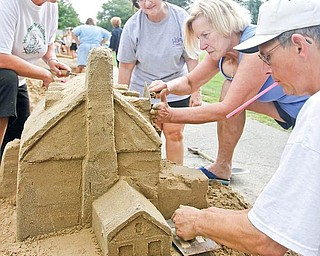 TAKING SHAPE: From left, Gladys Antonelli, Brenda Metz, Linda Miller and Mark Dolak of the Wednesday Walkers build a sand sculpture at Mill Creek MetroParks' annual Sunfest sand sculpting contest Sunday in the Wick Recreational Area near the Judge Morley Pavilion. Using photo references, they are working on a replica of The Pioneer Pavilion located in the park. The Wednesday Walkers also sculpted The Old Mill in the park, which took first prize in the Adult Division of the contest.