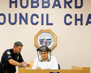 Hubbard Mayor Arthur U. Magee conducts mayor's court Monday with assistance from Hubbard Police Sgt. David Oaks. The mayor is wearing a halo after breaking vertebrae in his neck. The mayor said he tried staying home but feels he's better off doing something.