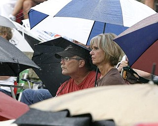 INTENTLY LISTENING - John VonMoos (37 years at Packard) ( warren) and Pat Stoner 35 -Niles - Years at Packard sit among a sea of umbrellas as they listen  at the Retirees Unite, Packard hourly retirees group, is meeting to rally the troops against pension cuts- robertkyosay