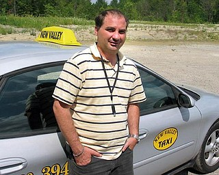 Robert Reizian, president of New Valley Taxi, stands by one of his cabs. Reizian says his employees are trained to avoid being robbed, but one employee failed to follow proper procedures when she was  robbed last weekend.