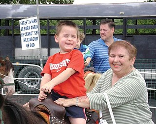 Nicholas McGoogan of Poland enjoys a pony ride at Our Lady of Mount Carmel Festival in Youngstown. With him is his grandmother, Anita Regula of Campbell.