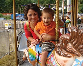 Anthony Coppola of Union, Ky., and his mom, Colleen, ride on the carousel at the Mount Carmel Festival in Lowellville.