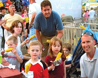 The Sweder family, enjoying corn on the cob at St. Nick's Festival in Struthers, includes Jeff and Christie of Poland with their three sons, Ryan, Jason and Evan of Poland, and Michael and his daughter, Riley, of Columbus.