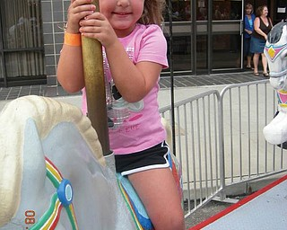 Samantha McKim of New Middletown couldn't resist the merry-go-round at the Greater Youngstown Italian Fest.