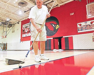 STAYING IN THE LINES: Marv Hermes, of Williams Hardwood Flooring in Akron, carefully maneuvers his paint roller along the taped lines on the new floor of Canfield High School's gymnasium. The crew was painting the lines on the new floor Friday.