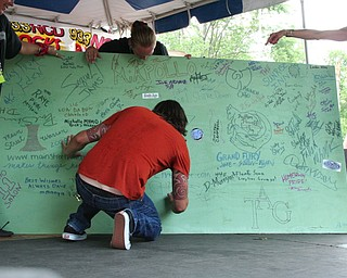 Dave Grohl signing the board at the David Grohl Alley dedication in Warren.