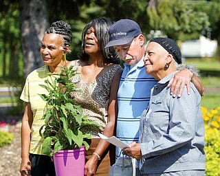 Willie Mae Johnson, far right, stands with her daughters, Sandra and Vickie, and son, William, as the family receives the Good Neighbor Award, a plant and gardening gloves Monday from Lien Forward Ohio. The Johnsons have been cleaning and landscaping vacant lots at Norwood Avenue and Wirt Street for the past three years.