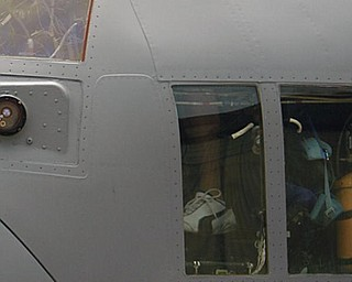 GHOST FLIGHT: Pavlik and daughter, Sydney, 4, peek out of the cockpit of the C-130. The artwork was unveiled at the base Tuesday.