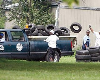 City workers remove tires collected and stacked as the Give the Children a Chance Choir and people from MCTA  cleared trees removed tires and debris mowed and planted gardens on Truesdale Avenue.