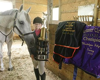 Madelynn Felgar with one of her trophys and horse blankets she won in 2009 with her horse - TOMMY - at their Beloit home - robertkyosay
