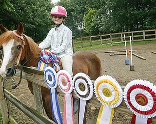Madelynn Felgar on her first pony with some of the many ribbons she has one in the last year  at their Beloit home - robertkyosay