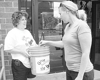 Special to The Vindicator BENEFIT: Joey Ewing Wolanzyk, a teacher and volunteer at the Rich Center for Autism at Youngstown State University, gets a kick out of making a donation to the Give Autism the Boot fundraiser, which is the center's major summer fundraiser. Accepting the contribution is Deb Maust, a parent volunteer.