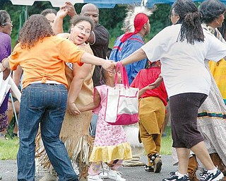 Dancers with the Red Hawk American Indian Cultural Society and people from the crowd at the Afrikan Cultural Weekend Fest dance to a native American song outside the Mill Creek Community Center Saturday, August 8th.