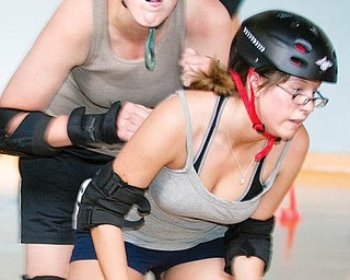 ROUGH SPORT: Darla Drummond tries to get past another roller derby participant in a recent roller derby practice. About 16 women are practicing within the league that began this past December. They hope to recruit others and eventually generate enough interest to create teams and begin competition.