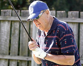 FORE-MAN: Joe Skebo, 78, of Youngstown, examines his club before teeing off. Skebo, who is visually impaired, plays with a group of golfers with similar ailments every week at the Par 3 Golf Course on McCollum Road.