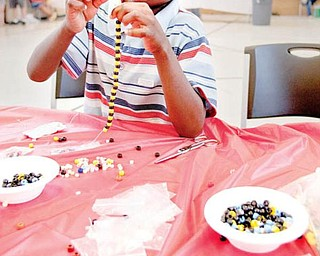 "Walter Talley, 6,  of Youngstown, makes a bracelet while at the ""Kids Fun Fair"" at The Salvation Army on Glenwood Ave., Wednesday afternoon."