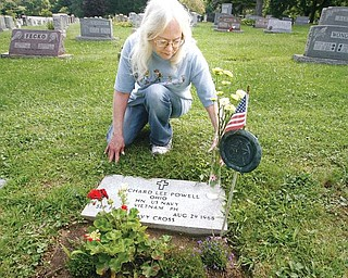 HERO'S STONE: Pattie Powell Scoville places flowers on the grave of her brother, Navy Corpsmen Richard Powell, who was killed in action in Vietnam. Powell is buried at Lake Park Cemetery on Midlothian Boulevard in Boardman.