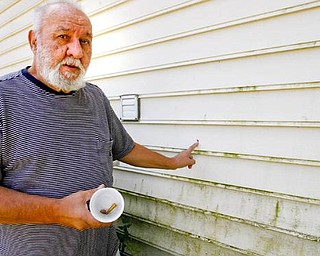ONE FAMILY'S STRUGGLE: Francis Humphries, of Albert Street, holds a bullet and shell casing he collected on his property after his home was recently hit with gunfire. He can point to the multiple bullet holes in the siding of his house and has taken to recording late-night activity around his home.