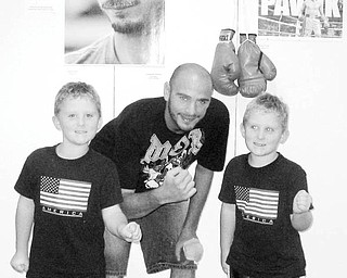 """Special to The Vindicator FAN APPRECIATION: Although they may be too young to bid on the photographs of the boxing champ, Kevin and Kyle Chopko enjoy having their pictures taken with Kelly """"The Ghost"""" Pavlik."""