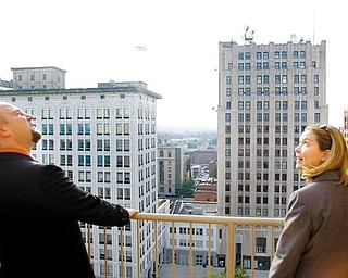 "Troy Miglets, of Austintown, looks up at the Realty Building from a balcony on the 11th floor, alongside Shanna Sallmen,  Development officer with ysu and resident of new castle. ""I just wanted to see the complex, see how they've progressed, its absolutely beautiful,"" said Sallmen."