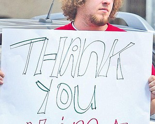 Tom Lordi holds a sign on Federal Street thanking V&M Star Steel.