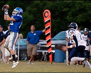 The Vindicator/Geoffrey HauschildLisbon's Tony Hunt (83) makes a catch before Leetonia's Justin Colella (10) can reach him during the second quarter at Lisbon. Leetonia went on to defeat Lisbon 41-7.8.27.2009