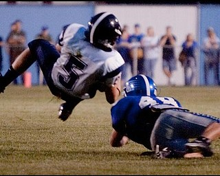 The Vindicator/Geoffrey HauschildLeetonia's Seth McNally is brought down by Lisbon's Robert Wilcox during the second quarter at Lisbon. Leetonia went on to defeat Lisbon 41-7.8.27.2009