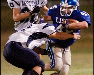 The Vindicator/Geoffrey HauschildLisbon's Robert Wilcox drives down the field thwarting a tackle by Leetonia's Devan Miller in front of teamate Dalton Scutt during the second quarter at Lisbon. Leetonia went on to defeat Lisbon 41-7.8.27.2009