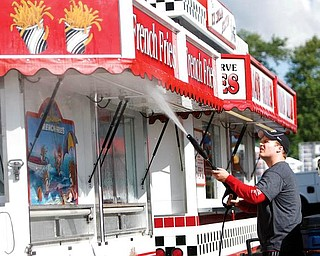 GETTING READY:  Jason Mechling, of Canfield, power washes his concessions trailer in preparation for the Canfield Fair, which begins Wednesday. Mechling says he has been working at the fair for longer than he cares to remember.