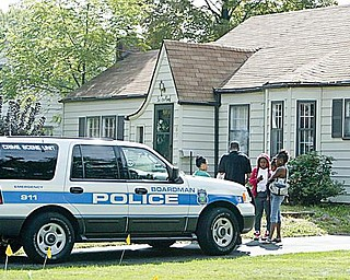 HOUSE RAIDED:  A Boardman police officer talks to people outside 65 Leighton Ave. in the township after officers and members of the U.S. Marshal's Special Task Force raided the home. Drugs and money were confiscated at the home Thursday morning.
