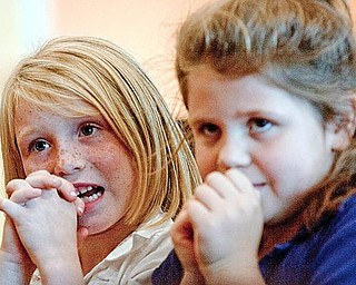 STORY TIME: First-graders Kailey May, left, and Shandi Coe listen to a story told by Regina Rees of Youngstown State University, who previously won the William Holmes McGuffey Historical Society's Pioneer Award.