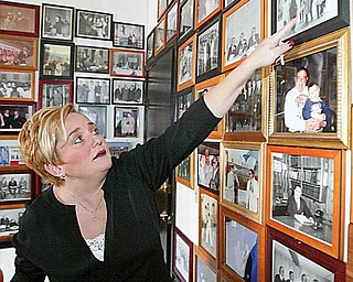 REMINISCING: Atty. Heidi Hanni looks over photos of her late father, Atty. Don L. Hanni Jr., with world and national leaders, on the walls of his office at 219 W. Boardman St. in downtown Youngstown. Unable to meet high building-maintenance and utility costs there, the Hanni law firm is moving to Boardman today.