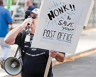 "CHANT LEADER: Rick Joseph, a member of the American Postal Workers Union Local 443, leads pickets Friday at the downtown post office as they chant, ""Save our service. Keep them open. SOS."""