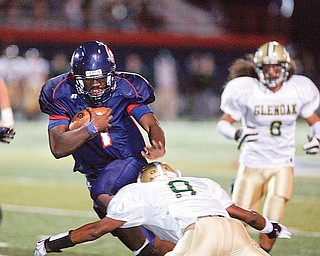 The Vindicator/Robert K. Yosay---  Fitch's  Jon Ballard breaks thru the line and a tackle by Glenoak  Brandon Martin during first  quarter action  at Fitch stadium - Ballard went on to score his 5th season rushing TD -9252009