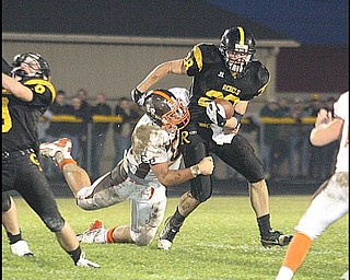 CRESTVIEW - EAST PALESTINE - (28) Andrew Mayer tries to get away from (60) Ben Gysin during their game Friday night. - Special to The Vindicator/Nick Mays