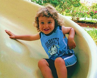 Carson John Arfaras, son of John and Lori Arfaras of Canfield, is enjoying playing on the slide when he was on vacation with his family.