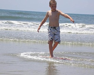 Jack McGlone, 7, is mastering the skim board at Ocean Isle Beach, N.C., in July.