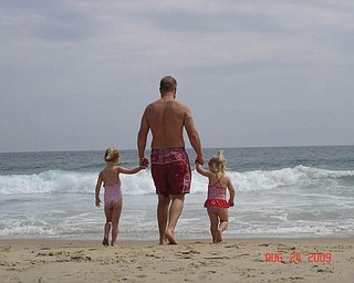 Brandon Bower of Austintown enjoys a stroll on the beach with his two girls, Brelyn, 4, and Kaelyn, 2.