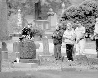 HISTORIC EVENT: Greg Ricker, points as he explains the life of J. Smith Cowden, who was buried in 1902 at Oak Hill Cemetery, near downtown Youngstown. Cowden was the third firefighter to die in the line of duty for the Youngstown Fire Department. Ricker, who is dressed as a firefighter, is part of the Mahoning and Shenango Valley Historical Club, which gave a presentation Saturday at the South Side cemetery.