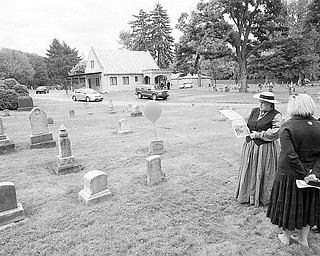 Judy Foster of Enon Valley, Pa., above right, wears a period costume as she talks to Sandy and Patrick Gatta of Poland about the life of Frederick Workman, a Gettysburg veteran who died in 1888. The Gattas said they are considering joining the historical club.