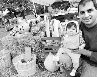 Carl Angiuli and his 8-month-old daughter, Gisella, above, pose near some gourds at a booth for Angiuli's Farm Market in Canfield.