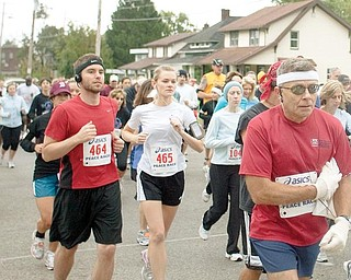 OFF AND RUNNING: Joe Scalzo, a Vindicator sports writer, left, runs his third Peace Race. Scalzo crosses the starting line Sunday on West Indianola Avenue with his wife, Tiffani, center, running her first 10-kilometer race.